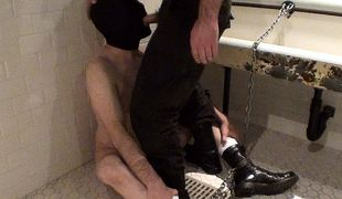 The prisoner patiently waits, chained to the urinal